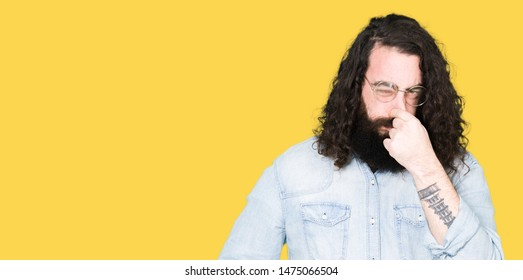 Young hipster man with long hair and beard wearing glasses smelling something stinky and disgusting, intolerable smell, holding breath with fingers on nose. Bad smells concept.