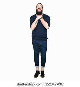 Young hipster man with long hair and beard wearing glasses shouting and suffocate because painful strangle. Health problem. Asphyxiate and suicide concept.