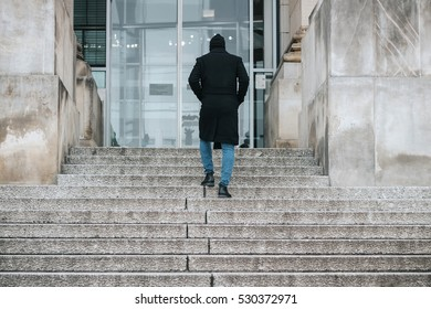 Young hipster man with long winter coat climbs up the stone stairs to the big building modern entrance