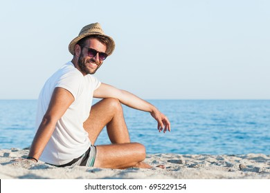 Young hipster man lying on the beach