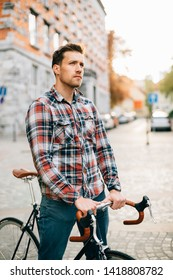 Young hipster man on fixie on the street before sunset