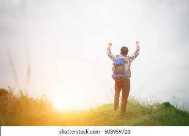 Young hipster man outdoor raising hands with backpack on his shoulder, Success Goal Adventure with hiking.
