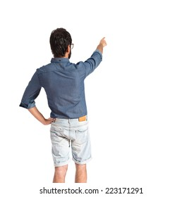 Young hipster man pointing back over white background