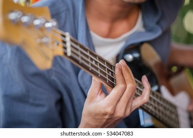 Young hipster man practiced guitar in the park,happy and enjoy playing guitar.