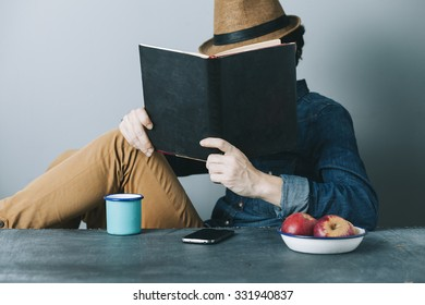 young hipster man reading a book and relaxing