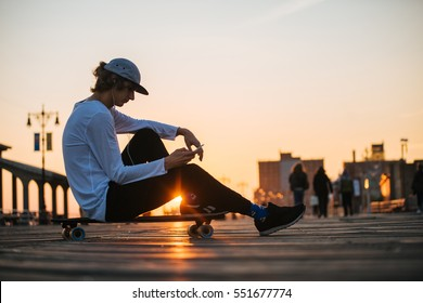 Young hipster man silhouette sitting on the longboard using his phone and headphones