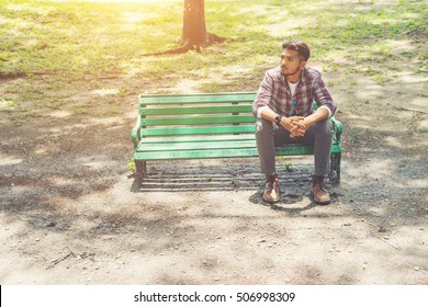 Young hipster man  sitting on a wooden bench in the park.