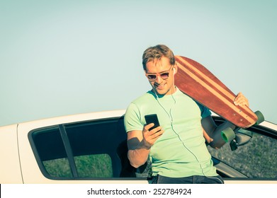 Young hipster man with smartphone listening music during trip break next his car - Concept of new trends and modern technologies mixed with a retro lifestyle - Soft desaturated vintage filtered look