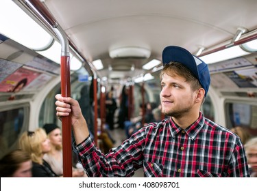 Young hipster man standing in a crowded subway train
