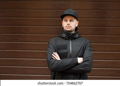 Young hipster man in stylish black baseball cap and winter jacket is standing near the wooden wall