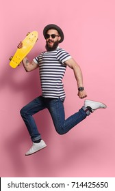 Young hipster man in sunglasses and hat holding yellow longboard and jumping on pink.