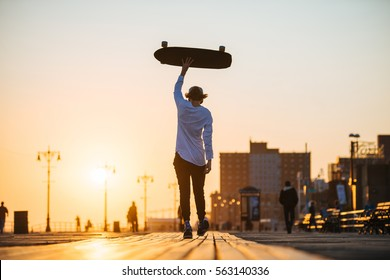 Young hipster man walking with longboard in hands on the boardwalk outside