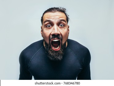"Young hipster man wearing casual blue t-shirt staring at camera with shocked look, expressing astonishment and shock, screaming ""Omg"" or ""Wow"". disappointment. Crazy emotions. surprise. Scream"