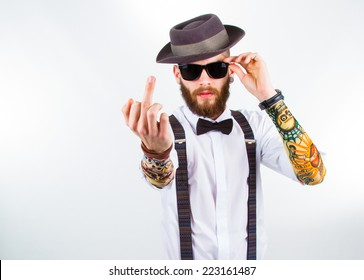 young hipster man wearing  hat , suspenders,   a bow-tie and   a funny tattoo-sleeve showing his f-finger
