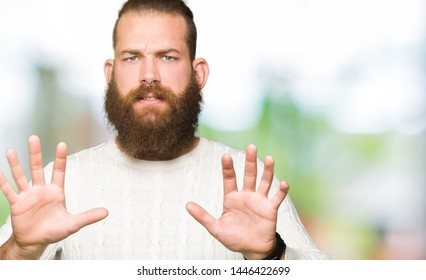 Young hipster man wearing winter sweater afraid and terrified with fear expression stop gesture with hands, shouting in shock. Panic concept.