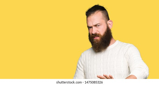 Young hipster man wearing winter sweater disgusted expression, displeased and fearful doing disgust face because aversion reaction. With hands raised. Annoying concept.