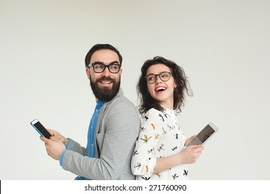 Young hipster man and woman in glasses with smartphone and tablet isolated on the blank white background