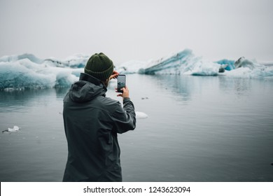 Young hipster or millennial adventurer with futuristic high technology all screen smartphone makes photo or video of impressive melting glaciers or icebergs in ice cold ocean water.