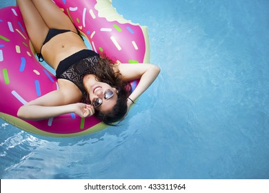 Young hipster millennial girl in sprinkled doughnut float at pool, festival, hotel, beach, event smiling with sunglasses on during summer