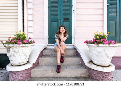 Young hipster millennial woman sitting smiling happy on stairs steps, front porch in New Orleans by colorful pink door architecture with yellow flowers in spring pot