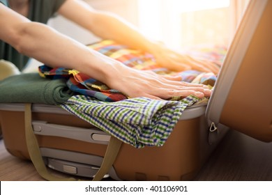 Young hipster packing his clothes and  stuff into large opened suitcase that almost already full, preparation for vacation or travel
