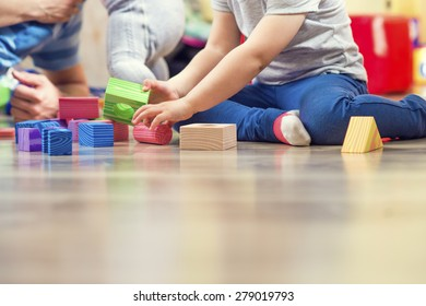 Young hipster playing with his daughters on a floor