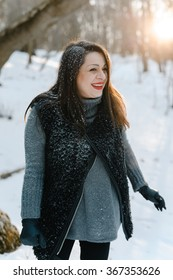 Young hipster pregnant lady smiles and enjoy winter sunset in a park covered with snow
