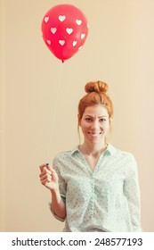 Young hipster redhead woman holding a red balloon with polka dot hearts