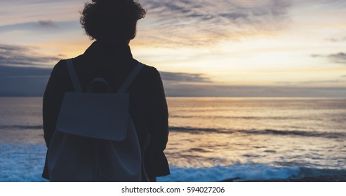 Young hipster relax on the beach on background ocean sunrise, silhouette romantic person look view evening seascape, girl enjoy sunset on coast, travel holidays vacation, back figure on backdrop sea