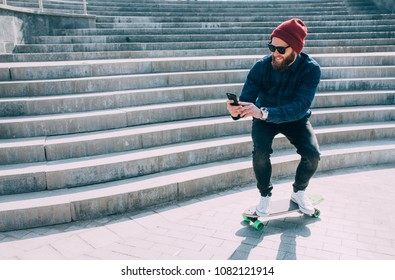 A young hipster rides a longboard and shoots a video on the phone. Photo on smartphone