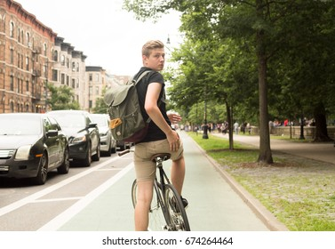 Young hipster riding bike looking back in the city, photographed in Brooklyn, NY in July 2017