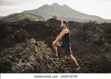 Young hipster runner with beard stretching and warming-up for trail running outdoors. Listening music in air pods. Mountain view on background.