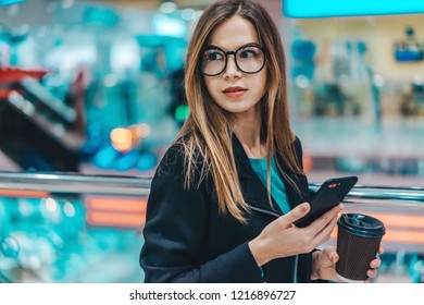 Young hipster shopaholic girl standing in shopping mall hall and typing message on mobile phone to friend boasting with her purchases while having coffee break after big sale day.