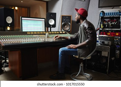 Young hipster sitting on chair in front of monitor and soundboard in studio of records