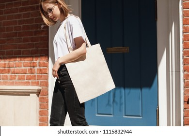 Young hipster smiling girl with white blank cotton shopper paper bag wearing white t-shirt and black jeans, mock-up of blank bag, brick wall and blue door on the background, concept of shopping