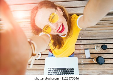 Young hipster student woman tourist with red lips making selfie photo sitting on the wooden bench outdoor. Positive laughing girl in yellow eyeglasses with laptop in sunny morning. Top view.