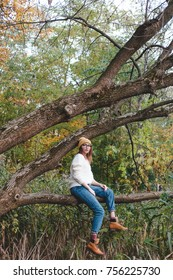 Young hipster style woman with glasses girl sitting on a tree in white warm pullover and yellow hat. Autumn style clothes.