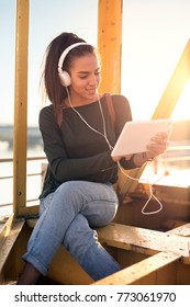 Young hipster stylish beautiful girl listening to music, digital tablet, headphones, enjoying, denim outfit, smiling, happy, sunrise, having fun, laughing