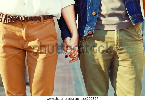 Young hipster stylish couple in love standing together. Holding hands.