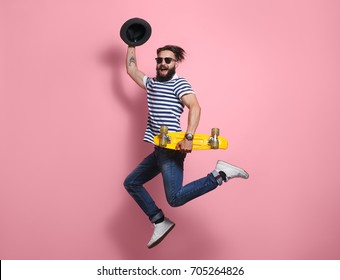 Young hipster stylish man in sunglasses and hat holding yellow longboard and jumping on pink background.