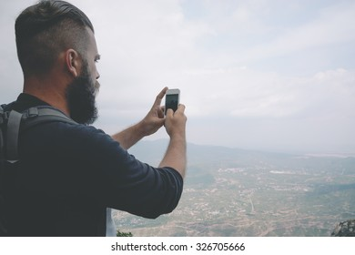Young hipster is taking photo by smart phone on the peak of mountain
