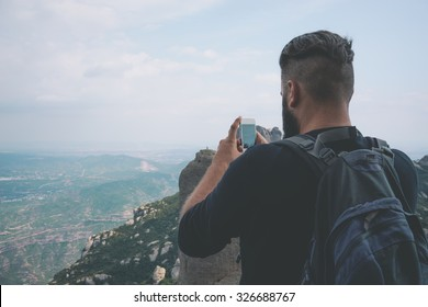 Young hipster taking picture with phone camera of landscape
