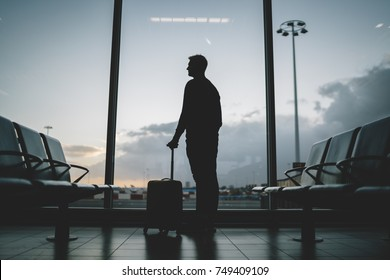 Young hipster tourist traveler standing in airport with suitcase waiting his flight, holidays concept