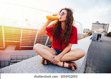 Young hipster woman with curly hair in sunglasses drinking fresh orange juice from bottle, spending time with pleasure outdoors.