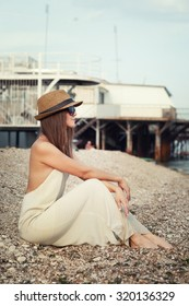 Young hipster woman dressed in white dress and hat sitting on a seacoast.