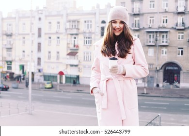 Young hipster woman is drinking coffee on the street while walking on cold winter day. Model wearing pink coat. Glamorous trendy outfit, accessories, hot latte, toned instagram colors.