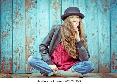 Young hipster woman with hat against wooden wall. outdoor shot. soft daylight toned old image