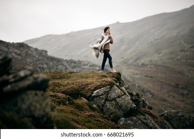 Young hipster woman hiker hiking on mountain trail. Travel concept. Traveler standing on top of a mountain. Hiker girl wrapping in warm poncho outdoor. Beautiful boho woman