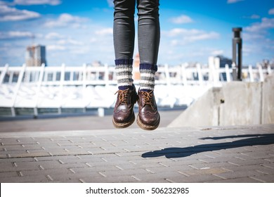 Young hipster woman jumps in the city