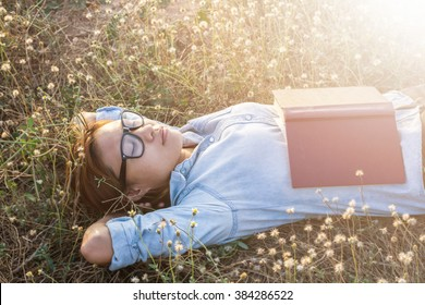 Young hipster woman lying in flower field after she tired for reading